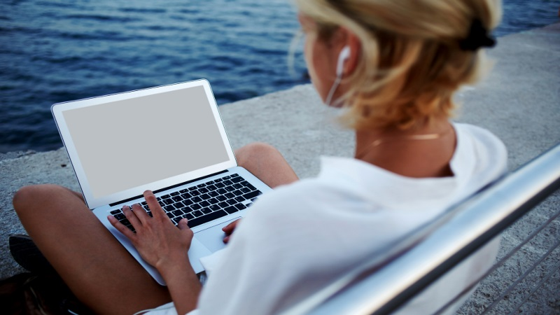Back view of young woman in headphones watching movie on laptop computer while sitting on pier near sea, female tourist using net-book with blank copy space screen for your text message or information